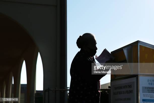 Virginia Garibay casts her vote at the Huntington Park Library ballot drop box in Huntington Park on October 29 2020 in Los Angeles California...