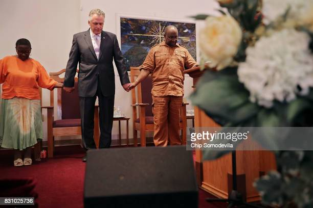 Virginia Gov Terry McAuliffe holds hands and prays with Dr Alvin Edwards pastor of Mt Zion First African Baptist Church August 13 2017 in...