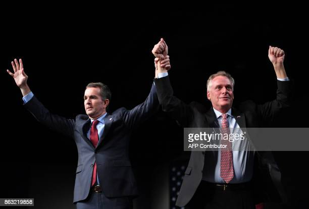 Virginia Governor Terry McAuliffe holds up the hands of Democratic Gubernatorial Candidate Ralph Northam during a campaign rally in Richmond Virginia...
