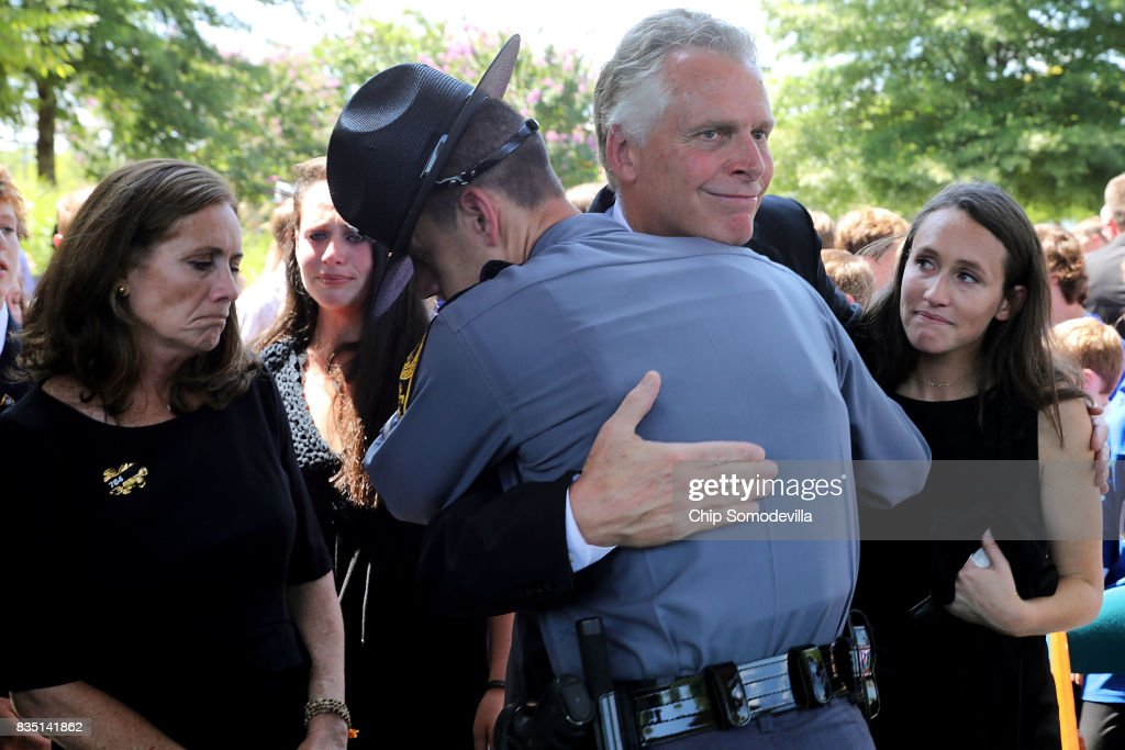 Virginia Governor Terry McAuliffe is embraced by a Virginia State Police trooper after he and his wife Dorothy McAuliffe (L) attended the funeral for Trooper-Pilot Berke M.M. Bates at Saint Paul's Baptist Church August 18, 2017 in Richmond, Virginia. Bates and Lieutenant Pilot Jay Cullen were killed when their Bell 407 helicopter crashed into a wooded area while they were monitoring the civil unrest during the white supremacy 'Unite the Right' rally August 12 in Charlottesville, VA.
