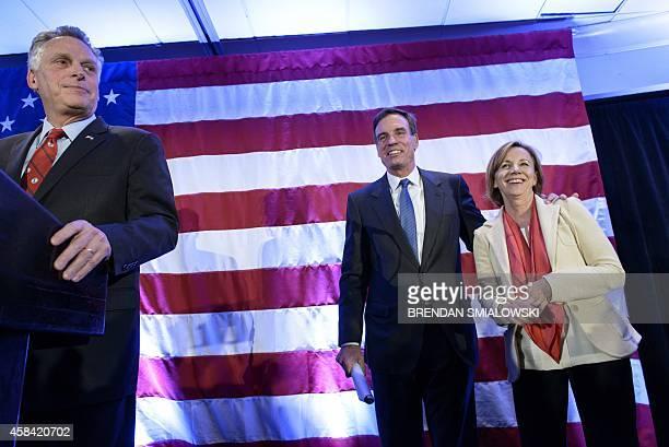 Virginia Governor Terry McAuliffe waits to speak as Virginia Democratic Senator Mark Warner and his wife Lisa Collis arrive for an election night...