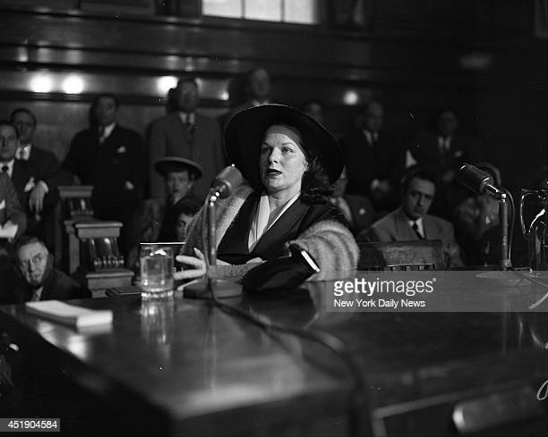 Virginia Hill ponders a question by Senator Kefauver sips a glass of water and then barks out an answer during her stretch on the witness stand...