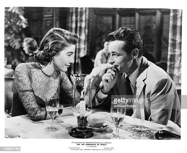 Virginia Leith reaching over to Guy Madison at table in a scene from the film 'On The Threshold Of Space' 1956