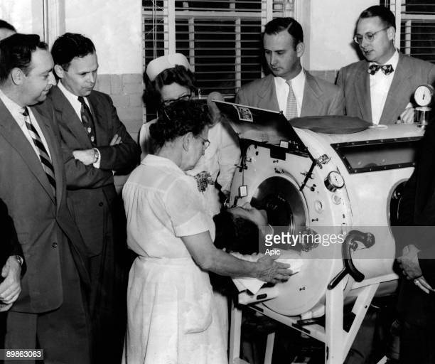 Virginia Lemke with her doctors in an iron lung device stimulating lungs activity to fight against the polio