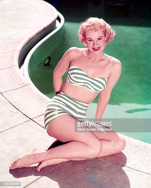 Virginia Mayo US actress wearing a greenandwhite striped bikini posing at the edge of a swimming pool circa 1945