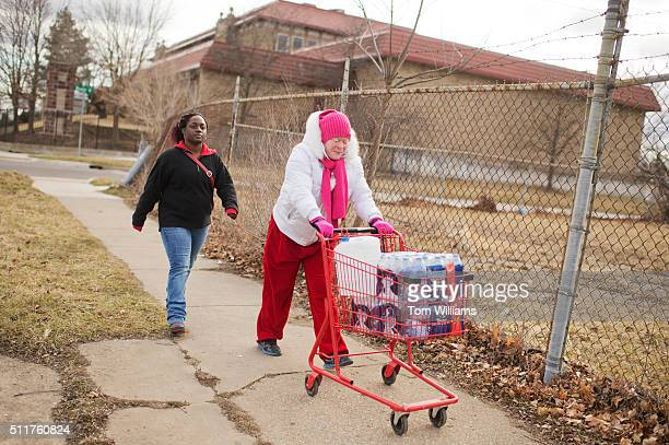 Virginia Mitchell right and her daughterinlaw Tiara Williams leave the the Sylvester Broome Center in Flint Mich after receiving cases of bottled...