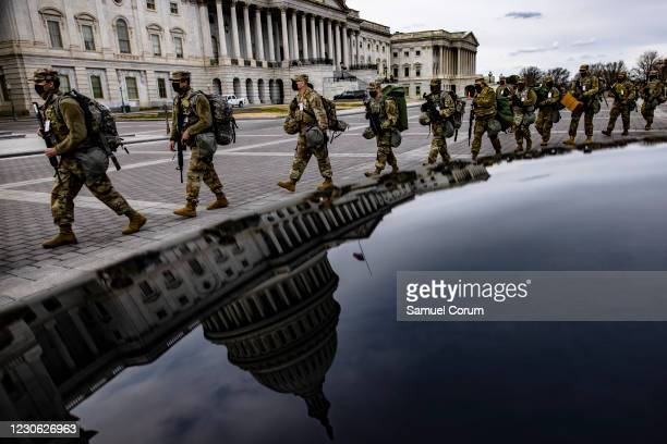 Virginia National Guard soldiers march across the east from of the U.S. Capitol on their way to their guard posts on January 16, 2021 in Washington,...