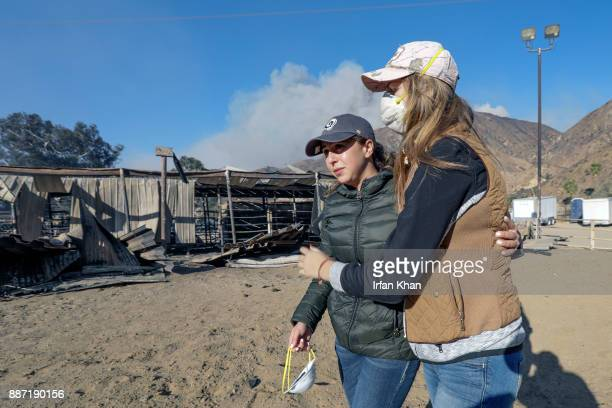 Virginia Padilla left who lost 29 horses at her Padilla Ranch on Little Tujunga Road is comforted by a horse trainer Shelby Hope Creek Fire swept...