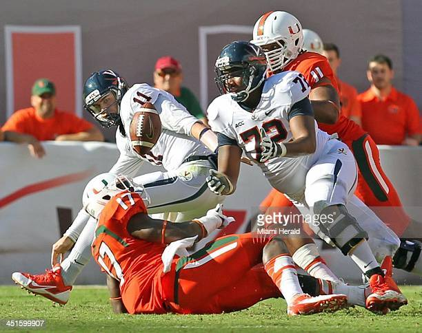 Virginia quarterback Ryan Williams fumbles the ball after getting stripped by Miami's Tyriq McCord in the fourth quarter at Sun Life Stadium in Miami...