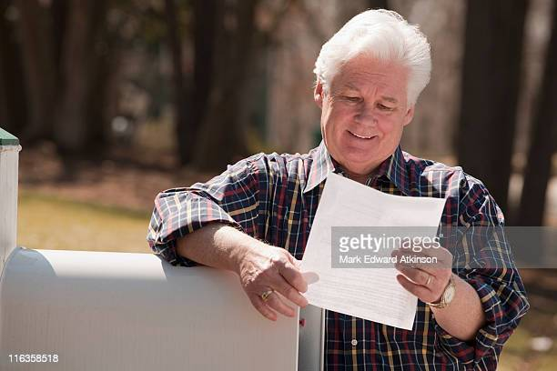 USA, Virginia, Richmond, senior man reading letter by mailbox