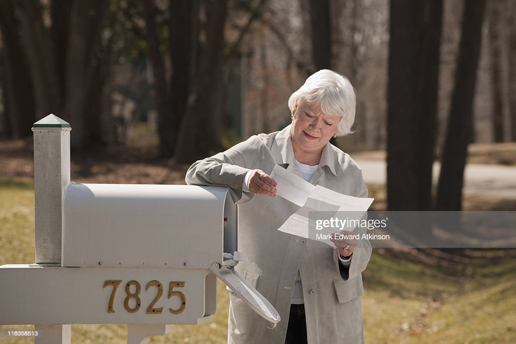 USA, Virginia, Richmond, senior woman reading letters by mailbox : Stock Photo