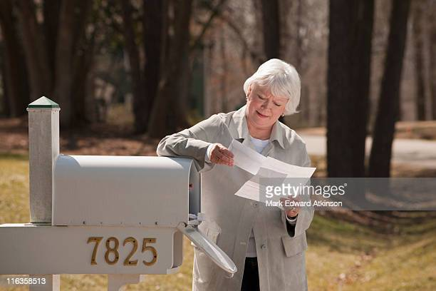 USA, Virginia, Richmond, senior woman reading letters by mailbox