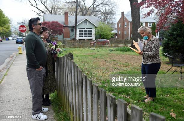 A Virginia state marriage officiant checks the marriage license of a couple before performing the ceremony while maintaining social distance due to...