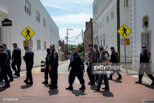 Virginia State Patrol officers cross the street August 10 2018 in Charlottesville near the makeshift memorial for Heather Heyer an activist killed by...