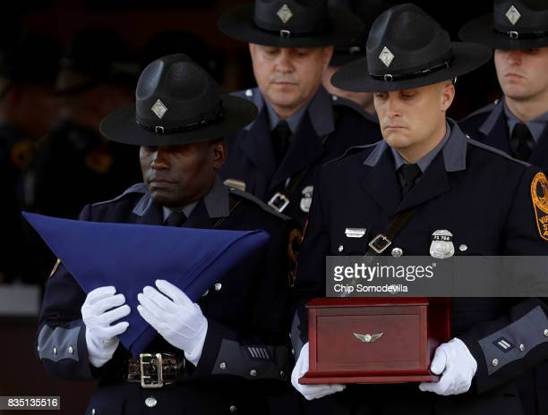 Virginia State Police honor guard carry the urn box with the remains of TrooperPilot Berke MM Bates's funeral out of Saint Paul's Baptist Church...