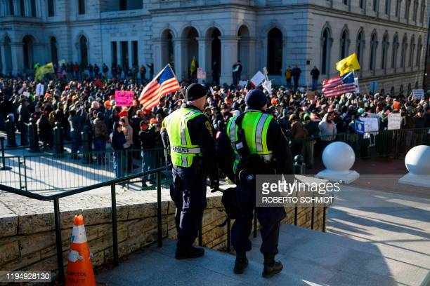 Virginia State police keep watch over a crowd gathered in front of the Virginia State Capitol in Richmond Virginia on January 20 2020 Several...