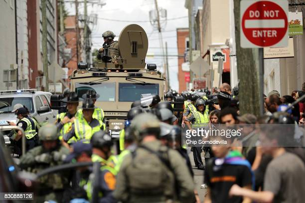 Virginia State Police officer in riot gear keeps watch from the top of an armored vehicle after car plowed through a crowd of counterdemonstrators...