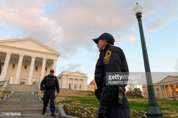 Virginia State police officers walk on the grounds of the Virginia State Capitol in Richmond Virginia on January 19 near a sign advising that an...
