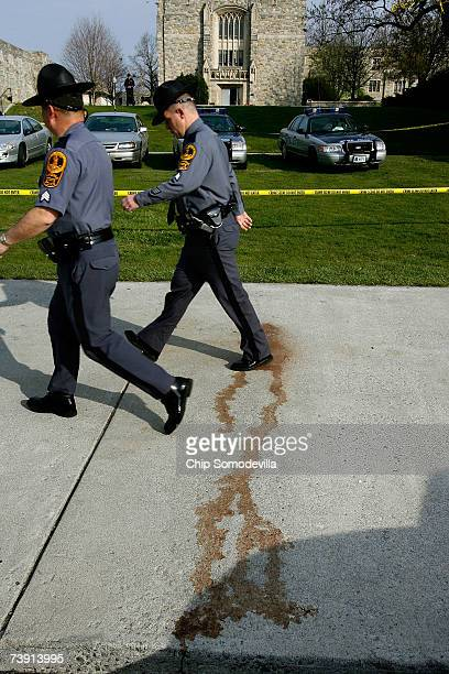 Virginia State police walk past a blood stain on the sidewalk outside Norris Hall after reports of a security alert on the campus of Virginia Tech...