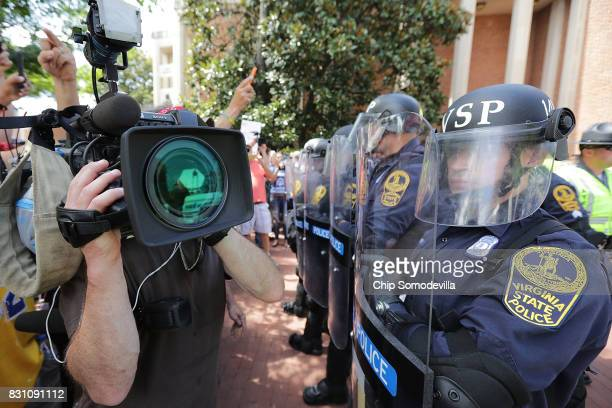 Virginia State Police wear body armor and use riot shields while keeping crowds away from altright blogger Jason Kessler after he tried to hold a...