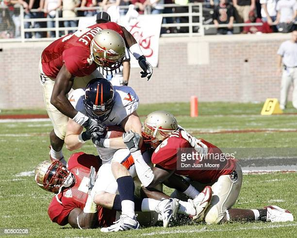 Virginia TE Tom Santi center is gang tackled by Florida State MLB Buster Davis left S Myron Rolle center and SLB Lawrence Timmons right during the...