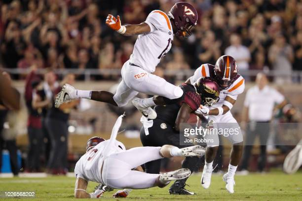 Virginia Tech Hokies defenders make a tackle in the first quarter of the game against Keith Gavin of the Florida State Seminoles at Doak Campbell...