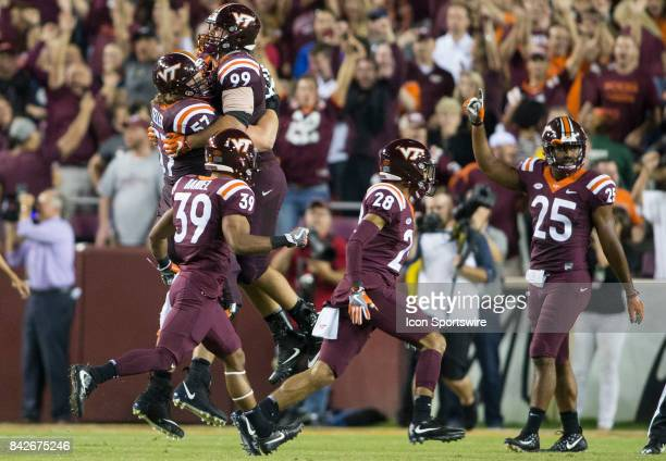 Virginia Tech Hokies defensive end Vinny Mihota and Virginia Tech Hokies guard Wyatt Teller celebrate at games end during a college football game...