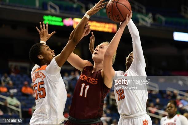 Virginia Tech Hokies forward Regan Magarity shoots between Clemson Tigers forward Tylar Bennett and Clemson Tigers guard Aliyah Collier during the...