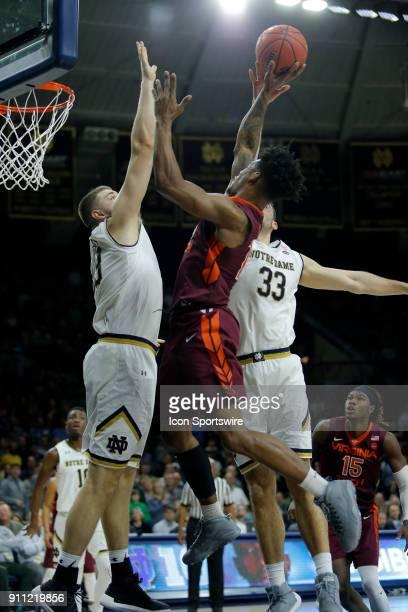 Virginia Tech Hokies guard Ahmed Hill goes up between Notre Dame Fighting Irish forward Martinas Geben and Notre Dame Fighting Irish forward John...