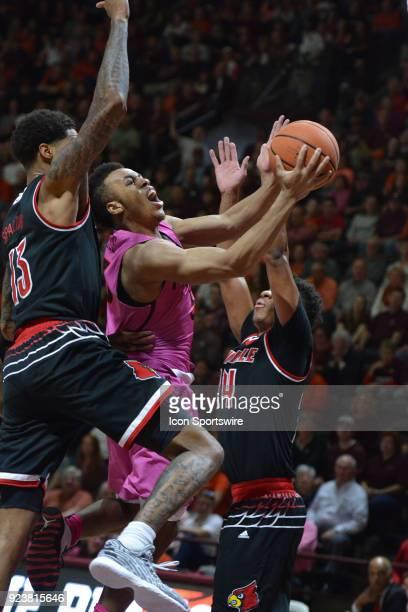 Virginia Tech Hokies guard Wabissa Bede goes in for a shot between Louisville Cardinals forward Ray Spalding and Louisville Cardinals forward Anas...