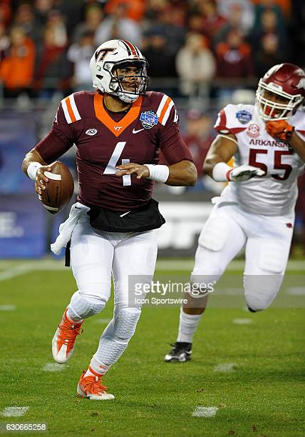 Virginia Tech Hokies quarterback Jerod Evans scrambles out of the pocket as Arkansas Razorbacks defensive lineman Jeremiah Ledbetter chases from...