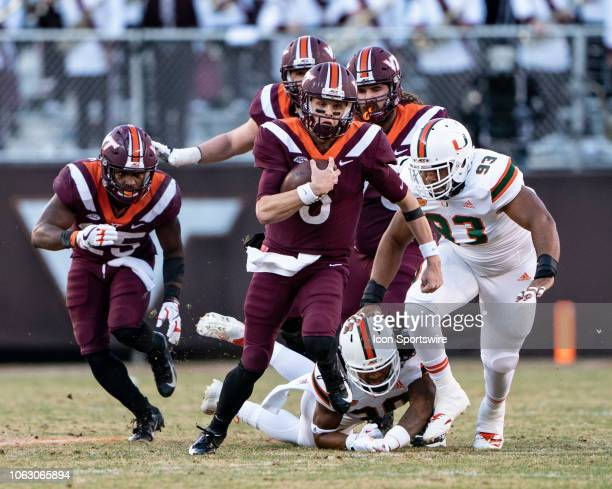 Virginia Tech Hokies Quarterback Ryan Willis runs the ball with Miami Hurricanes Defensive Lineman Pat Bethel in pursuit during the second quarter of...