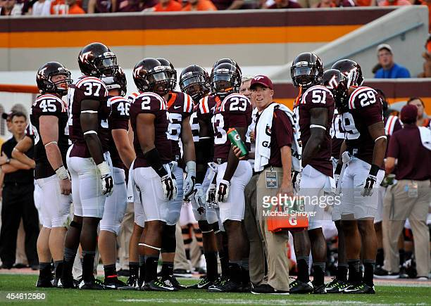 Virginia Tech players watch an instant replay on the stadium's video screen in the second half at Lane Stadium on August 30 2014 in Blacksburg...
