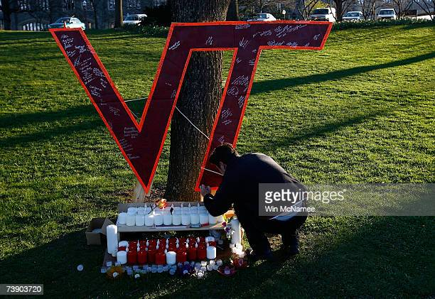 Virginia Tech student Daniel Hamilton writes on a memorial constructed on the Virginia Tech campus for the victims of yesterday's mass killings April...