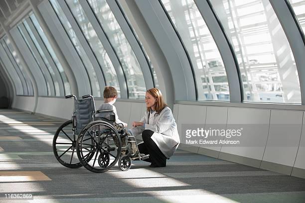 USA, Virginia, Virginia Beach, female doctor talking to boy (6-7) in wheelchair