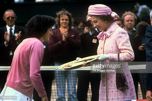 Virginia Wade curtseys to HM Queen Elizabeth II as the latter hands over the Ladies' Singles trophy to the champion