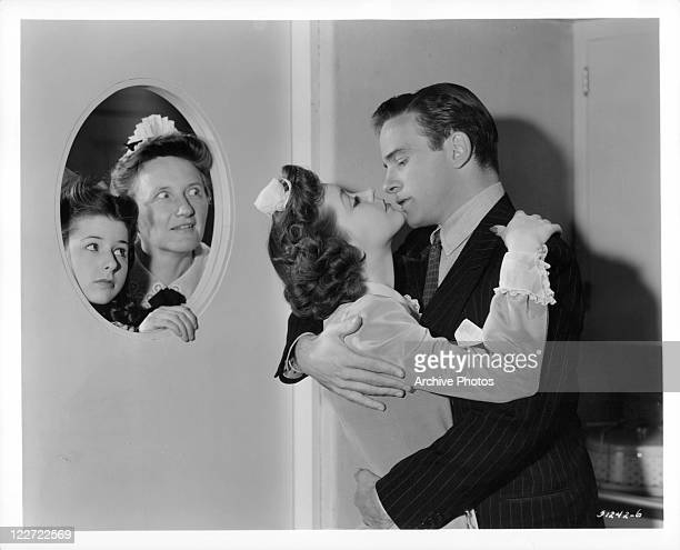 Virginia Weidler and Marjorie Main are looking through a door window in a scene from the film 'The Affairs Of Martha' 1942