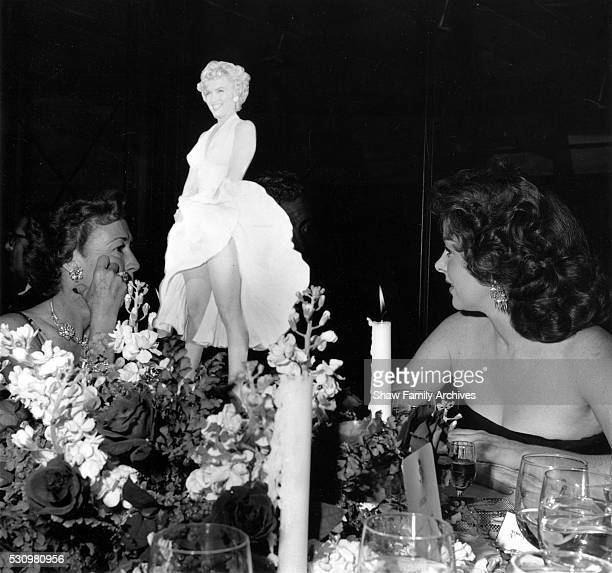 Virginia Zanuck wife of producer Darryl Zanuck and Susan Hayward sit at a table with a cutout of Marilyn Monroe at the wrap party for the filming of...