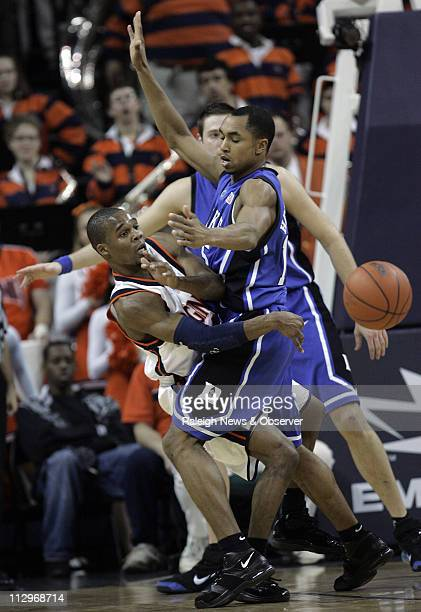 Virginia's Sean Singletary dishes off a pass as Duke's Gerald Henderson and Josh McRoberts defends during the first half at John Paul Jones Arena in...