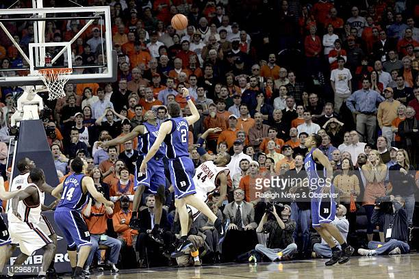 Virginia's Sean Singletary shoots the gamewinning basket in the final seconds of overtime past Duke's DeMarcus Nelson and Josh McRoberts to seal the...