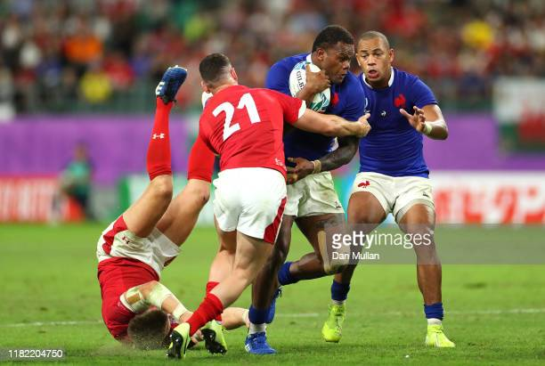 Virimi Vakatawa of France is tackled by Tomos Williams and Hadleigh Parkes of Wales during the Rugby World Cup 2019 Quarter Final match between Wales...