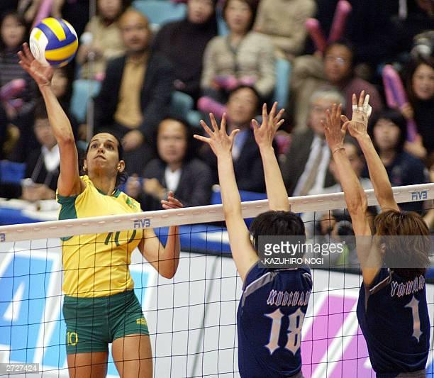 Virna Dias of Brazil hits the ball over Japanese defenders, Megumi Kurihara and Tomoko Yoshihara , during the World Cup women's volleyball tournament...