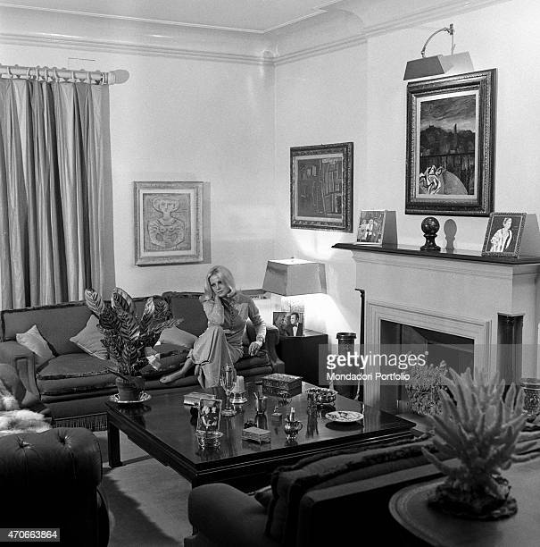 Virna Lisi in her living room seated on a sofa below a Campigli painting and by the fireplace a photo of her with husband Franco Pesci is placed on...