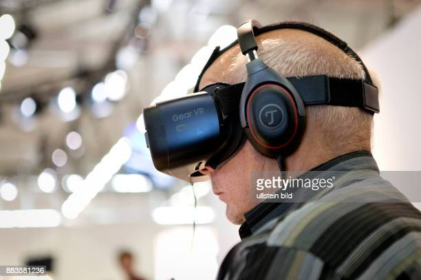 Virtual and augmented reality at the Photokina in Cologne: Man with a virtual reality Head-Mounted Display.