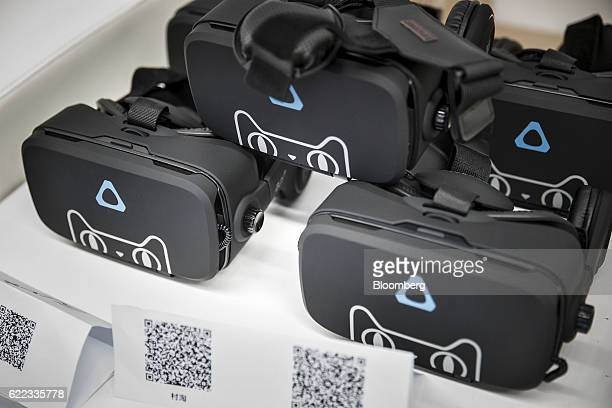 Virtual reality headsets featuring the Tmall Cat mascot for Alibaba Group Holding Ltd's Tmall online marketplace sit on display at Alibaba's annual...