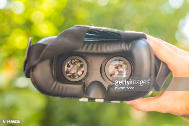 Virtual reality helmet natural background, outdoors activity. VR headset. Virtual reality glasses.