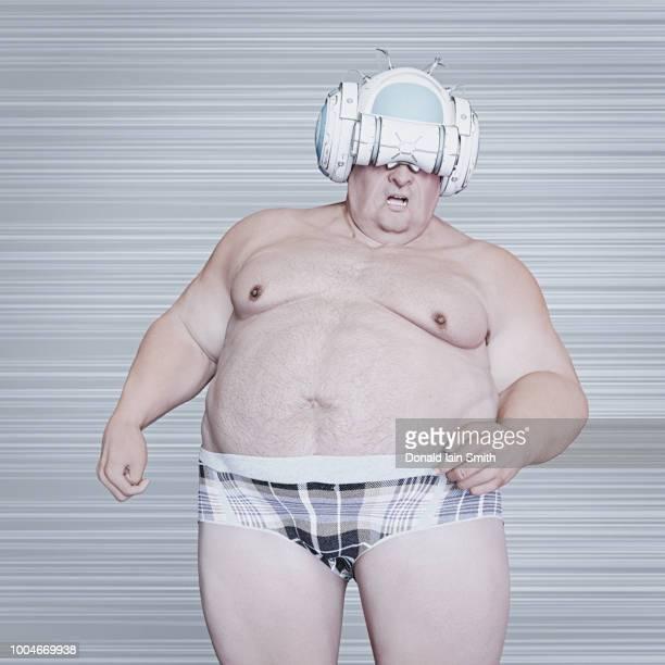 Virtual worlds: older fat man wearing VR helmet and underpants
