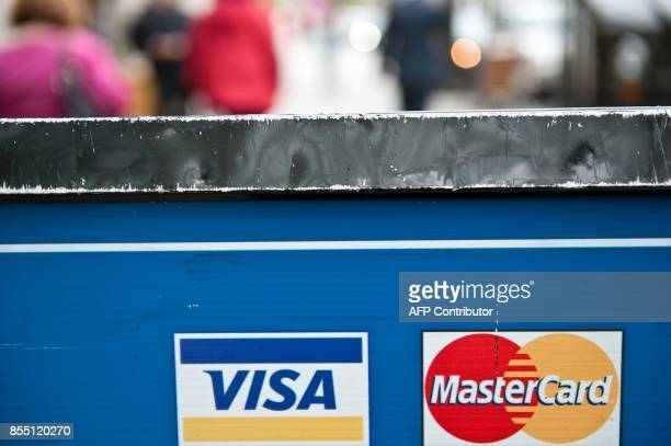 Visa and MasterCard credit card logos are seen in a store window in Washington on March 30 2012 Credit card giants Visa and MasterCard were...