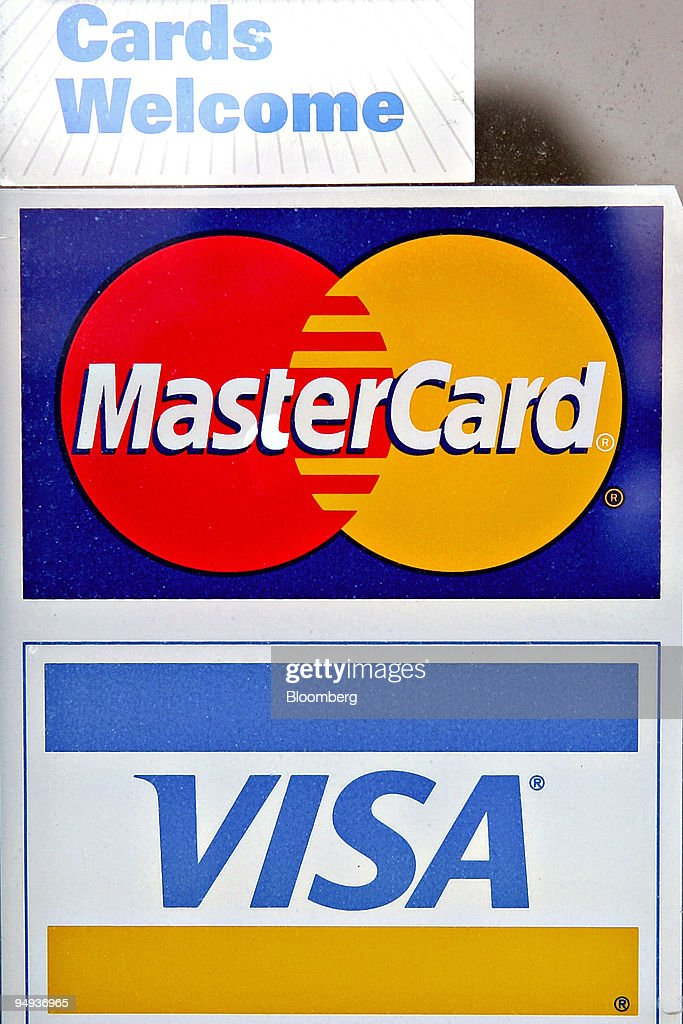 Visa And Mastercard Credit Card Signs Are Displayed In A Store