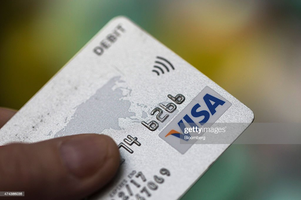 Visa Inc. and contactless payment logos sit on a debit card in this arranged photograph, in London, U.K., on Friday, May 22, 2015. Credit and debit cards that can be used by tapping the reader are gaining users, and mobile apps are set to further boost the popularity of contactless paying. Photographer: Simon Dawson/Bloomberg via Getty Images